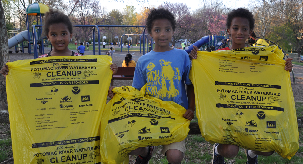 Three children sit on playground fence holding bright yellow trash bags.
