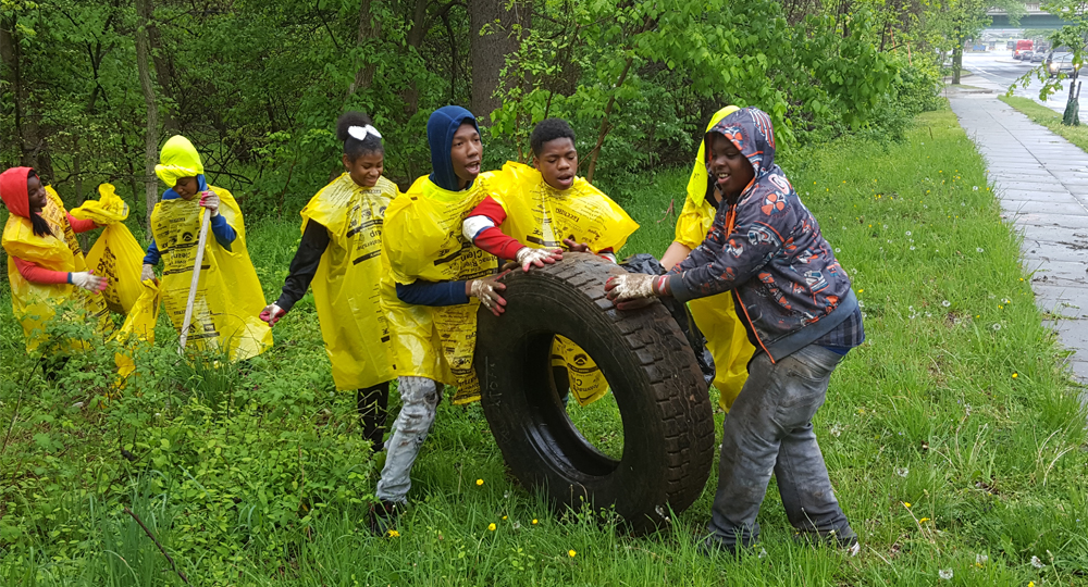 Group of kids in bright yellow vests roll a discarded tire out of the woods and towards a road.